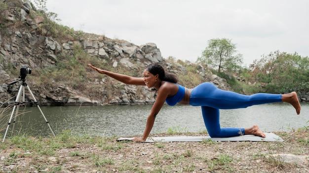 Donna che insegna ai suoi studenti pose di yoga