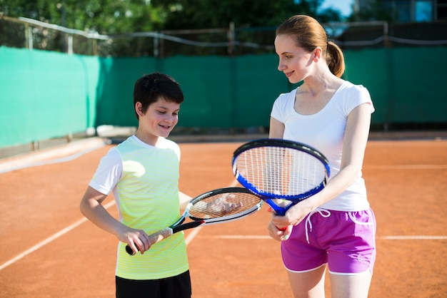 Woman teaching kid how to hold a tennis racket