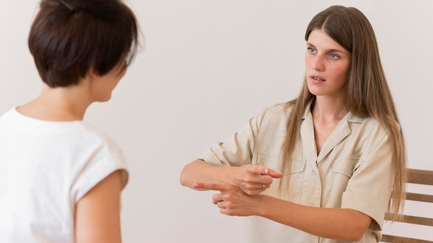 Женщина преподает язык жестов другому человеку
