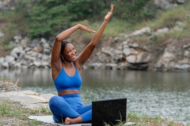 Woman teaching yoga to people online