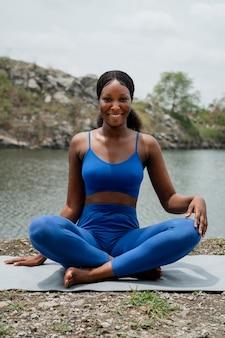 Woman teaching a yoga pose outdoors