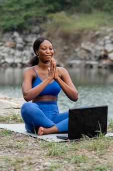 Женщина преподает йогу людям онлайн
