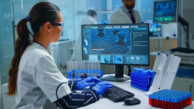 Женщина-технолог делает лабораторный тест, исследуя колбу с образцом крови, химик держит трубку с жидкостями внутри. ученый, работающий с различными тканями бактерий и изображением сканирования днк на компьютере