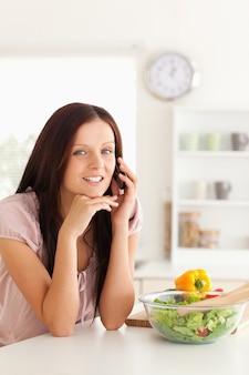 テーブルで電話する女性