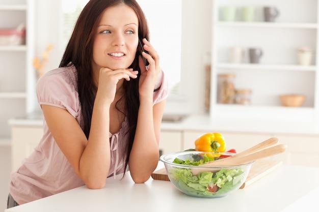 女性、台所で電話する