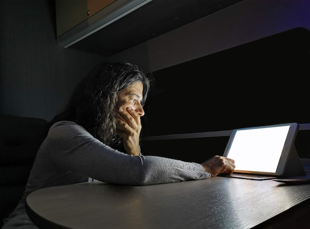 A woman teleworking from her motorhome at night