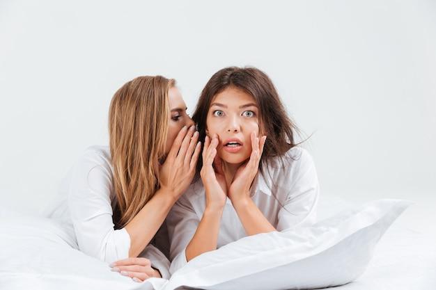 베개를 베고 침대에 누워 있는 동안 여자 친구에게 험담을 하는 여자