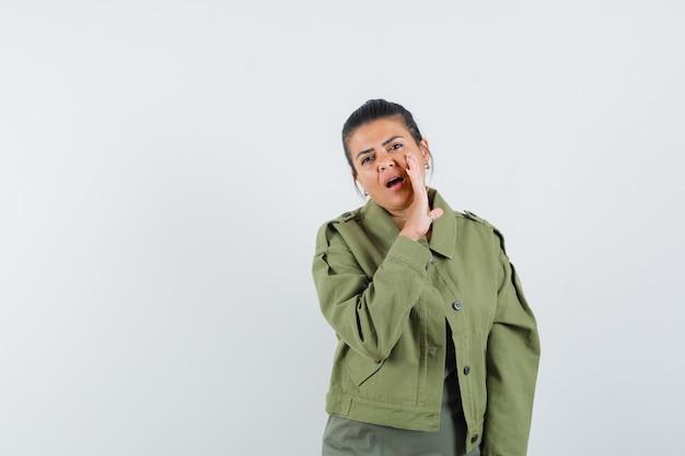 Donna che dice il segreto dietro la mano in giacca, t-shirt.