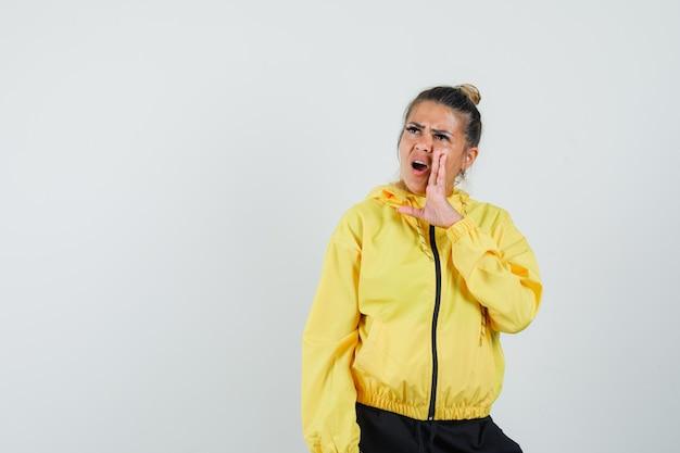Donna che dice il segreto dietro la mano in tuta sportiva e sembra confusa. vista frontale.