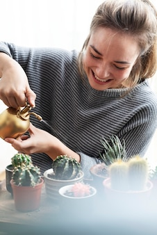 Donna che si prende cura e cura dei suoi cactus