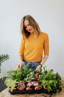 彼女の植物の世話をしている女性