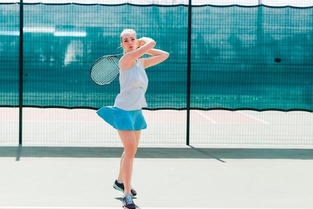 コートでテニスラケットを保持している白いドレスとかかとの女性テニスプレーヤー。若い女性はテニス、スポーツをしています