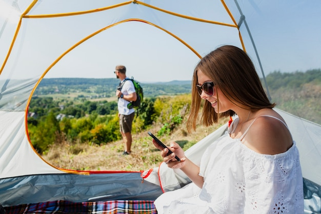 Woman in tent looking at her phone
