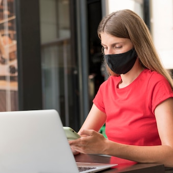 Woman at terrace working with face mask