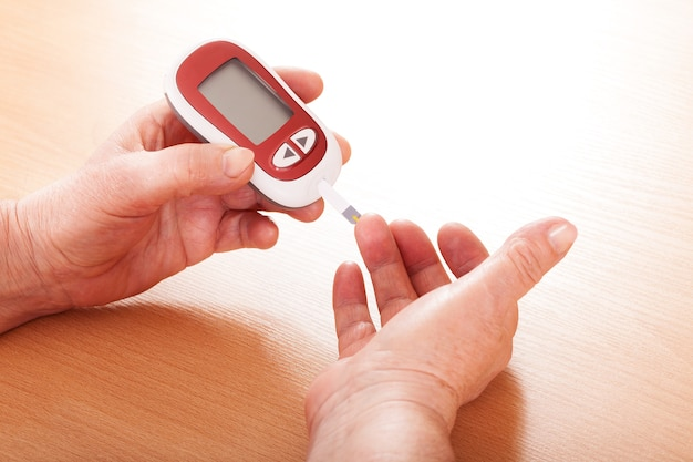Woman testing for blood sugar, hands closeup