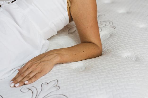 Женщина тестирует матрас в мебельном магазине