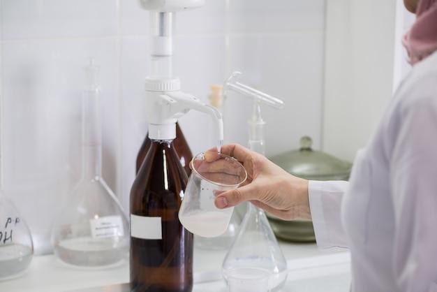 実験室で乳製品のサンプルをテストする女性。製乳工場の試験所