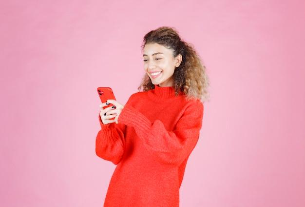 Donna che scrive al suo nuovo smartphone e si sente felice.