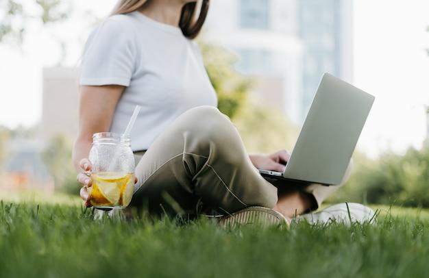 Женщина текстовых сообщений ноутбука, сидя на траве