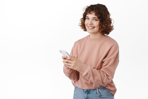 女性のテキストメッセージメッセージ、スマートフォンモバイルアプリの使用、カメラで幸せな笑顔、メッセージング、アプリケーションでのチャット、白の上に立っています。