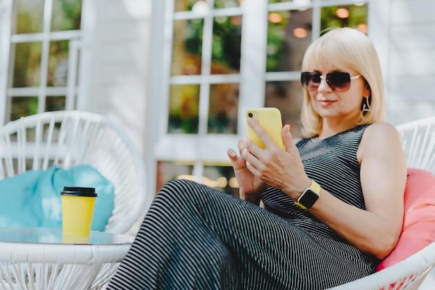 携帯電話でオンラインメッセージをテキストメッセージで送信する女性