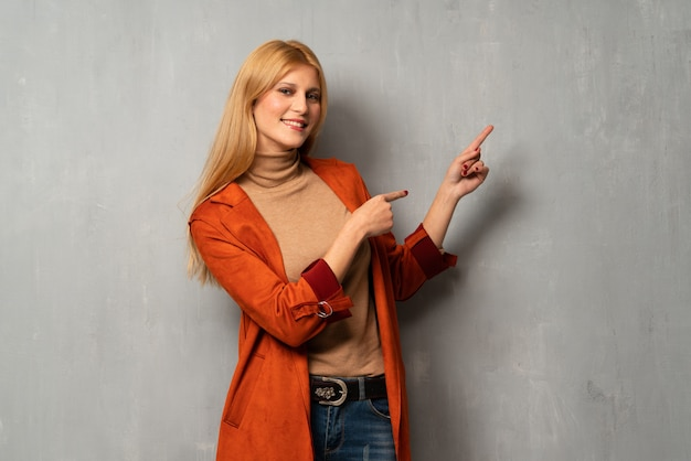 Woman over textured background pointing finger to the side in lateral position