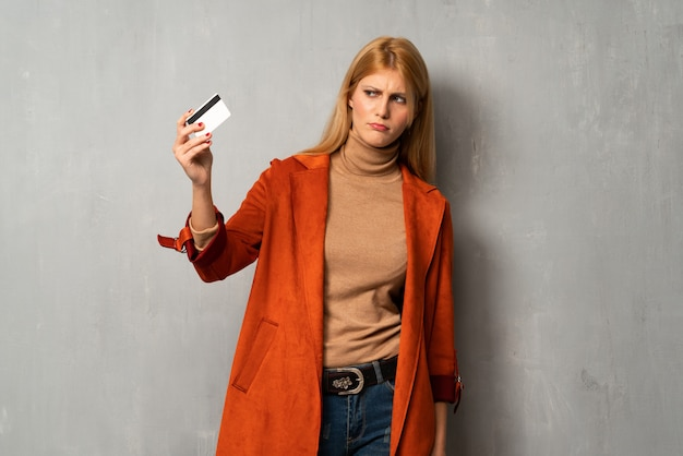 Woman over textured background with troubled holding broken smartphone