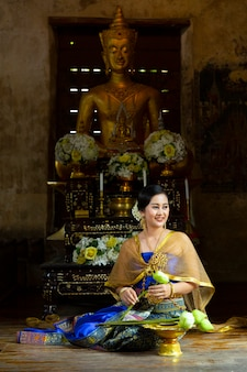 A woman in a thai dress is sitting to fold the lotus flower to offer the monks in the temple.