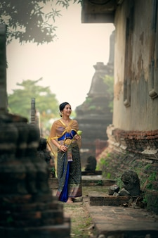 A woman in a thai dress is walking holding a lotus flower to present the monks in the temple.