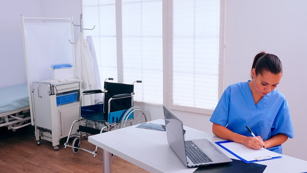 Woman therapist sitting at workplace looking at laptop reading news and taking notes on clipboard. medical physician in medicine uniform writing list of consulted, diagnosed patients, making research.