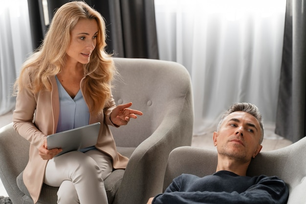 Woman therapist talking to man laying on couch