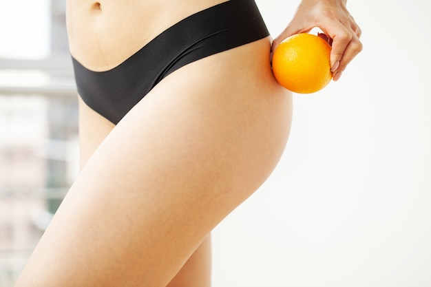 Woman thigh and leg with perfect skincompare an orange peel with her body.