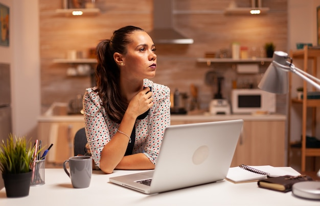 自宅のキッチンで深夜に締め切りに取り組んでいる間、自分のキャリアについて考えている女性。深夜に最新のテクノロジーを使用して、仕事、ビジネス、忙しい、キャリア、ネットワーク、活気のある時間外労働をしている従業員