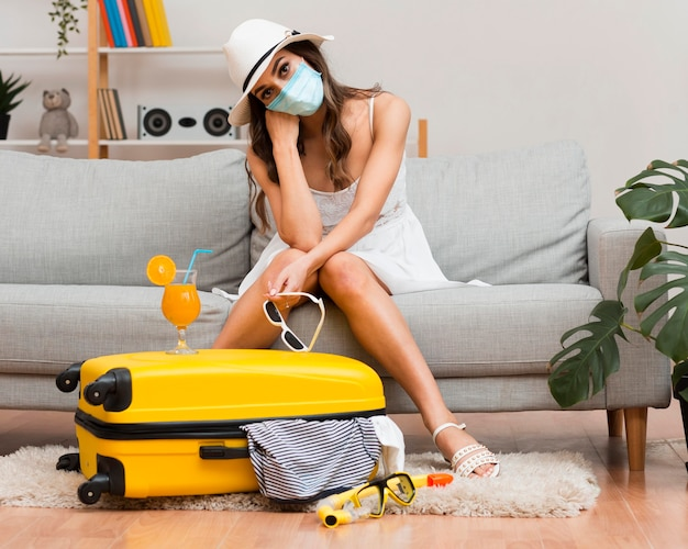 Woman thinking about her postponed holiday while wearing a medical mask