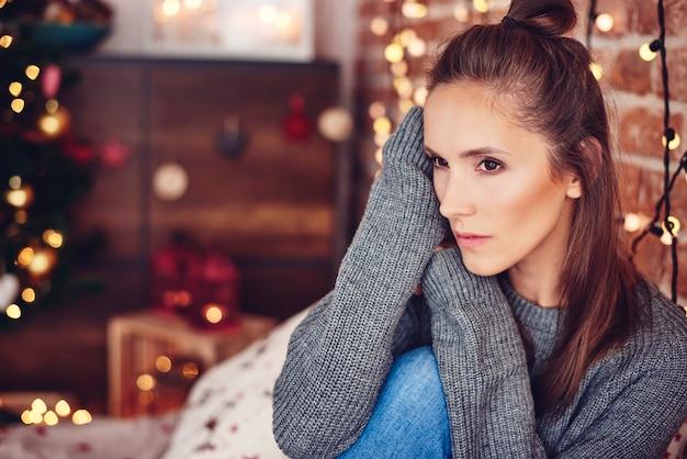 Женщина думает дома с рождественскими огнями на стене