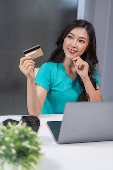 Woman thinking and holding credit card with laptop on table