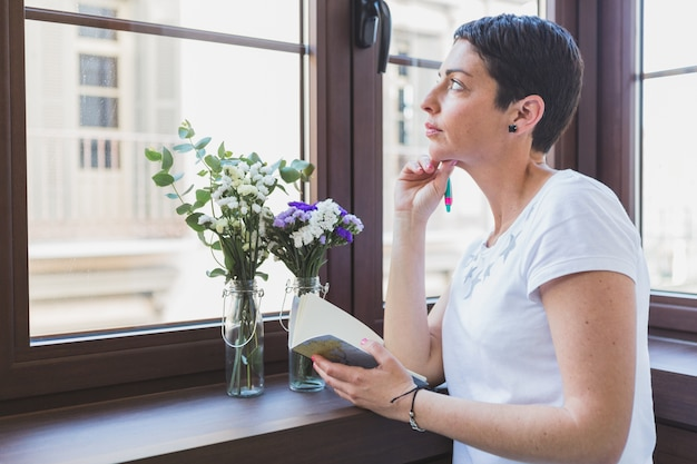 Woman thinking and looking through the window