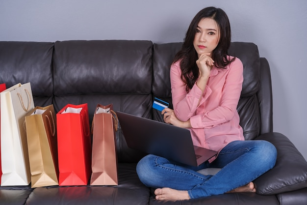 Woman thinking and using laptop computer for online shopping with credit card in living room