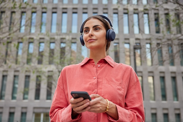 Woman thinks about something while listening music in headphones holds mobile phone wears red shirt strolls in ancient city against modern establishment