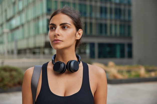 Woman thinks over personal training plans dreams to become new qualified dressed in sportsclothes practices yoga or pilates walks to fitness centre or health club stands in downtown