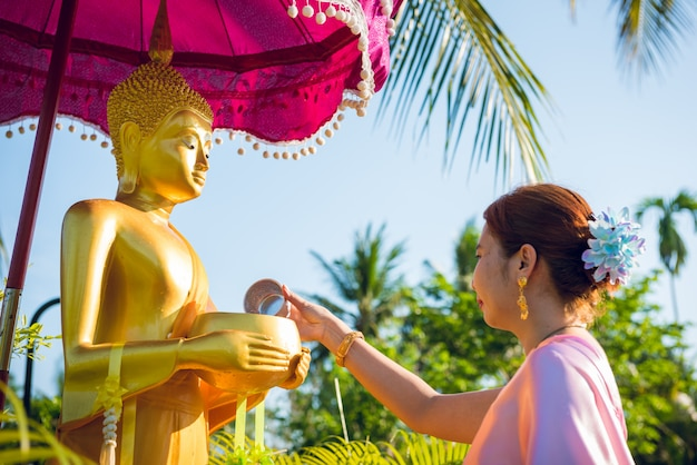 A woman this wearing traditional thai dresses are pouring water the buddha statue on the occasion of songkran festival day