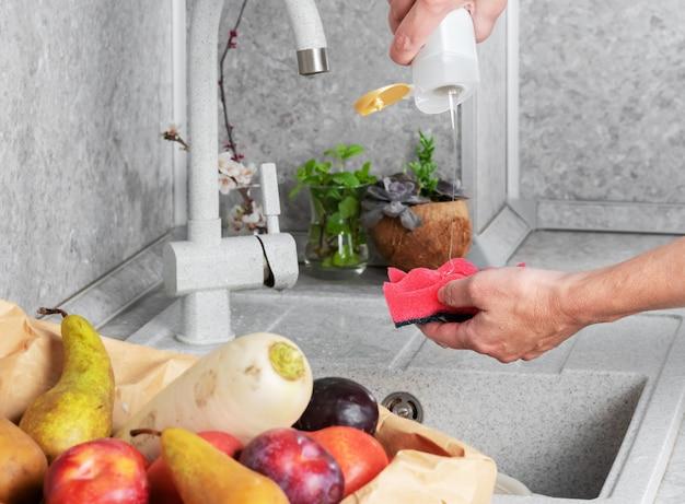 店で買い物をした後、果物や野菜を徹底的に洗う女性。個人衛生のコンセプト、ウイルスやバクテリアとの戦い。クローズアップ、ヘルスケア