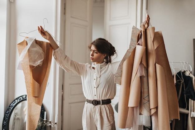 Donna che guarda pensierosa i suoi modelli di abbigliamento