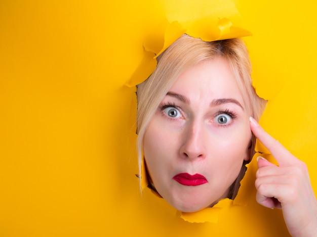 Женщина через дырку в желтой бумаге показывает, что ты сумасшедший