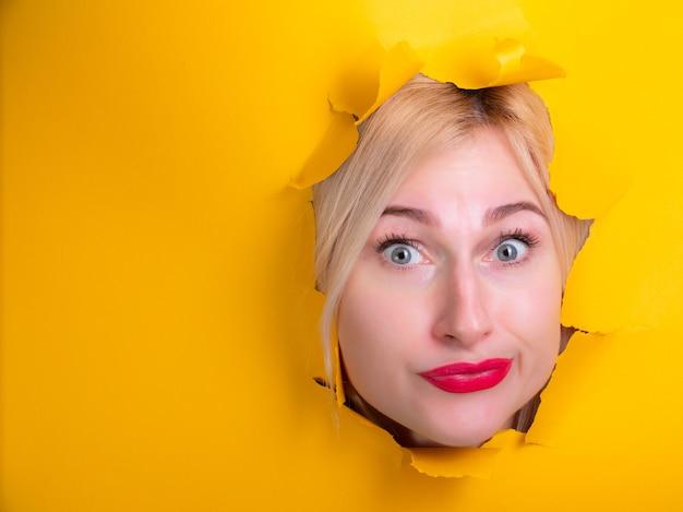 Женщина через отверстие желтой бумаги мышления