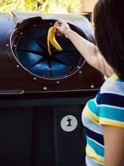 ゴミ箱にバナナの皮を投げる女性