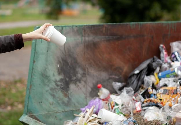 Женщина бросает картонный стакан в мусорное ведро. забота о чистоте города и окружающей среды. большой мусорный бак в общественном парке