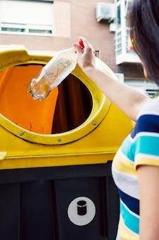 Женщина, бросающая бутылку в мусорное ведро