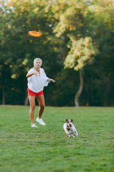 緑の草の上でそれを捕まえる小さな面白い犬にオレンジ色のフライングディスクを投げる女性。公園で屋外で遊ぶリトルジャックラッセルテリアのペット。野外で犬と飼い主。