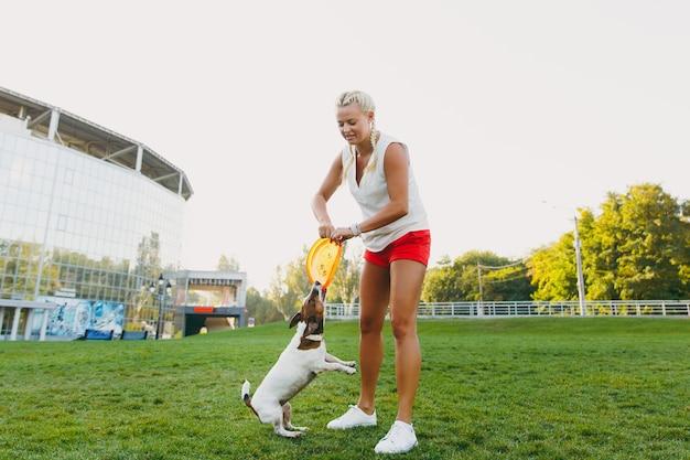 녹색 잔디에 그것을 잡는 작은 재미 개에 오렌지 비행 디스크를 던지는 여자. 작은 잭 러셀 테리어 애완동물이 공원에서 야외에서 놀고 있습니다. 야외에서 개와 소유자입니다.
